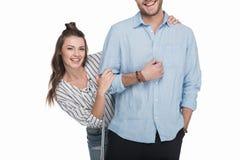 Pares jovenes felices que se colocan de abarcamiento y sonrientes en la cámara Imagen de archivo libre de regalías