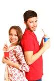 Pares jovenes felices que se colocan de nuevo a posterior y que beben de las tazas Imagen de archivo