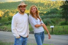 Pares jovenes felices que se colocan en zona rural. Imagen de archivo libre de regalías