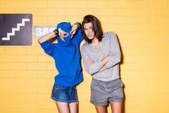 Pares jovenes felices que se divierten delante de la pared de ladrillo amarilla Foto de archivo