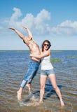 Pares jovenes felices que se divierten en el agua del mar fotos de archivo