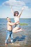 Pares jovenes felices que se divierten en el agua del mar fotos de archivo libres de regalías