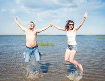 Pares jovenes felices que se divierten en el agua del mar foto de archivo libre de regalías