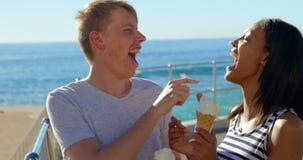 Pares jovenes felices que se divierten mientras que teniendo helado cerca de las verjas 4k almacen de video