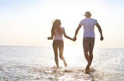 Pares jovenes felices que se divierten que corre en la playa en la puesta del sol Imágenes de archivo libres de regalías