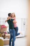 Pares jovenes felices que se mueven en nueva casa Foto de archivo