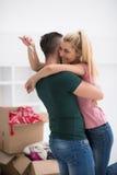 Pares jovenes felices que se mueven en nueva casa Fotos de archivo libres de regalías