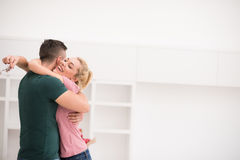 Pares jovenes felices que se mueven en nueva casa Imagenes de archivo
