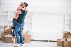 Pares jovenes felices que se mueven en nueva casa Imagen de archivo libre de regalías