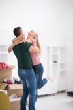 Pares jovenes felices que se mueven en nueva casa Fotografía de archivo libre de regalías