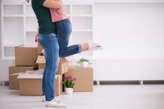 Pares jovenes felices que se mueven en nueva casa Imágenes de archivo libres de regalías