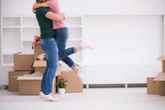 Pares jovenes felices que se mueven en nueva casa Imagen de archivo