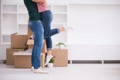 Pares jovenes felices que se mueven en nueva casa Fotos de archivo