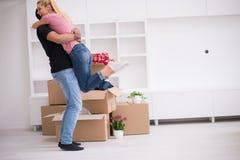 Pares jovenes felices que se mueven en nueva casa Fotografía de archivo