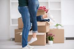 Pares jovenes felices que se mueven en nueva casa Foto de archivo libre de regalías