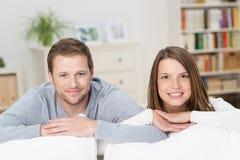 Pares jovenes felices que se relajan en casa Foto de archivo libre de regalías