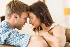Pares jovenes felices que se relajan en el sofá Imagen de archivo