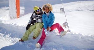 Pares jovenes felices que se relajan en un estante de la nieve imagen de archivo