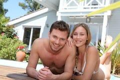 Pares jovenes felices que se relajan por la piscina Imágenes de archivo libres de regalías