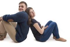 Pares jovenes felices que se sientan de nuevo a la parte posterior Fotos de archivo libres de regalías