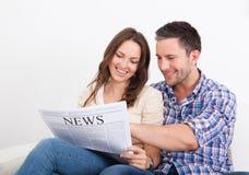 Pares jovenes felices que se sientan en el periódico de la lectura del sofá Fotos de archivo