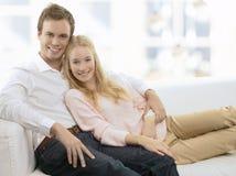 Pares jovenes que se relajan en el sofá Imagen de archivo libre de regalías