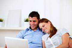 Pares jovenes felices que se sientan en el sofá con una computadora portátil Fotografía de archivo libre de regalías