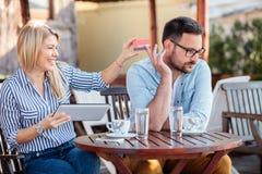 Pares jovenes felices que se sientan en un café y que hacen compras en línea Mujer que toma la tarjeta de crédito de su novio imagenes de archivo