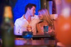 Pares jovenes felices que se sientan en un club nocturno, sonriendo Fotos de archivo libres de regalías