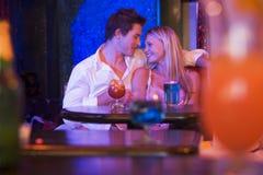 Pares jovenes felices que se sientan en un club nocturno, sonriendo Imágenes de archivo libres de regalías