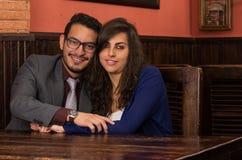 Pares jovenes felices que se sientan en un restaurante Fotografía de archivo