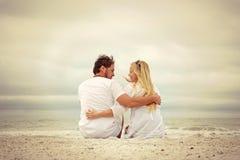 Pares jovenes felices que se sientan por el océano en la playa imagen de archivo libre de regalías