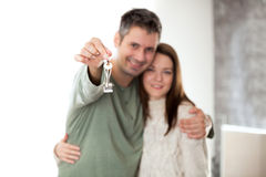 Pares jovenes felices que se trasladan a un nuevo hogar Imagen de archivo libre de regalías