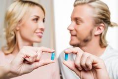 Pares jovenes felices que sostienen píldoras y que se sonríen Imagenes de archivo