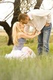 Pares jovenes felices que tienen un beso romántico al aire libre en campo verde imagenes de archivo