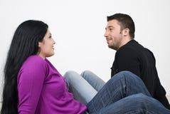 Pares jovenes felices que tienen una conversación Imagen de archivo libre de regalías
