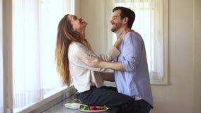 Pares jovenes felices que tienen vinculación de risa de la diversión en la cocina metrajes