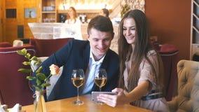 Pares jovenes felices que toman el selfie con el teléfono elegante en el café metrajes