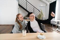 Pares jovenes felices que toman el selfie con el teléfono elegante en el café en alameda copie el espacio para su texto imagen de archivo