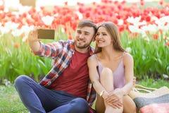 Pares jovenes felices que toman el selfie en parque el día de primavera imágenes de archivo libres de regalías