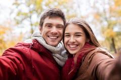 Pares jovenes felices que toman el selfie en parque del otoño Foto de archivo libre de regalías