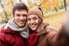 Pares jovenes felices que toman el selfie en parque del otoño Foto de archivo
