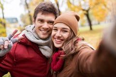 Pares jovenes felices que toman el selfie en parque del otoño Imágenes de archivo libres de regalías