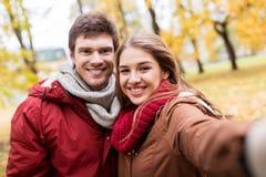 Pares jovenes felices que toman el selfie en parque del otoño Fotografía de archivo