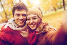 Pares jovenes felices que toman el selfie en parque del otoño Imagen de archivo