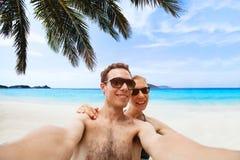 Pares jovenes felices que toman la foto del selfie en la playa foto de archivo libre de regalías