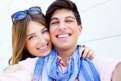 Pares jovenes felices que toman las fotos con un smar Imagen de archivo libre de regalías