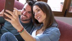 Pares jovenes felices que toman un selfie con el tel?fono elegante mientras que se sienta en el sof? en casa almacen de video