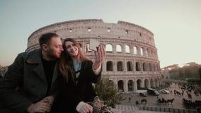 Pares jovenes felices que toman una foto del selfie cerca del Colosseum en Roma, Italia El hombre hermoso besa a la mujer, sonrie metrajes