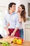 Pares jovenes felices que trabajan en cocina Imagen de archivo